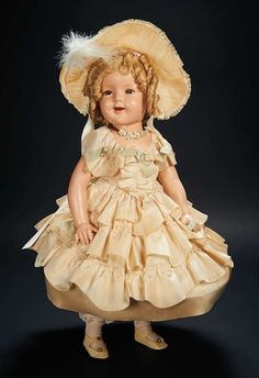 "Shirley Temple's Ideal circa 1935 Composition Doll of Shirley Temple in ""The Little Colonel"" Costume -27"" composition w/hazel sleep & flirting eyes, human hair lashes, open smiling mouth with row of teeth and dimpled cheeks, blonde mohair ringlet-curled wig, jointing at throat, shoulders & hips. The doll is wearing her very elaborate original costume comprising elaborately tiered taffeta gown with hooped petticoat, pantalets, socks, shoes, matching feathered bonnet, and floral garland necklace Z"