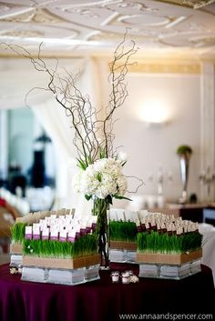Here, the escort cards are part of the centerpiece. Cards are stuck in wheat grass. Center is curly willow and hydrangeas. annanandspencer.com is the photographer.