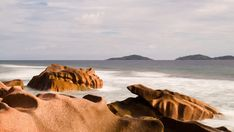 A static early morning timelapse of granitic rocks and waves crashing in the sunlight on La Digue, near Anse Fourmis beach with Felicite and Marianne island in the background. Rock Formations, Travel And Tourism, Early Morning, Geology, High Quality Images, Stock Footage, Sunlight, Rocks, Tropical