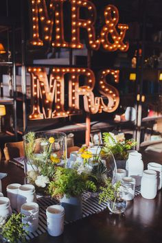 Terrariums + White Painted Mason Jars | Wedding Centerpieces | Mr. & Mrs. Lighted Sign | On SMP: http://stylemepretty.com/2013/11/27/smog-shoppe-wedding-from-sitting-in-a-tree-events | Photography: rad and in love  - www.radandinlove.com