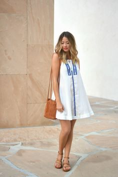 Allie (@alliewears) wears THML Clothing's white embroidered halter dress in a summer ready outfit.