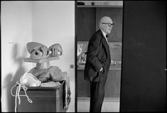 """Rene Burri LE CORBUSIER, painter, urbanist & architect. 1959. FRANCE. Paris. 16th arrondissement. 24, rue Nungesser-et-Coli. Apartment-atelier Le Corbusier (1931-1934). Le Corbusier, by the entrance to the kitchen, next to the sculpture """"Les mains"""", which he created in 1956 with Joseph SAVINA. 1959."""