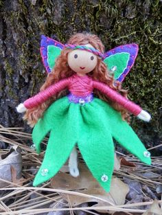 Handmade Miniature Green Waldorf Flower Fairy Princess Doll...beautiful handcrafted flower fairy princess. She is dressed in a pink top, green skirt adorned with sparkling beads and a purple belt. Her outfit is complete with beautiful handstitched purple fairy wings outlined with pink stitching, green centers and shinny beads. She stands at just over 4 inches...
