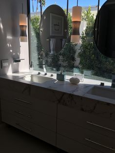 Master bath in marble with floating round mirrors at the Christopher Kennedy Compound in Palm Springs