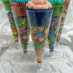 Plastic champagne glasses filled with candy topped with a cupcake