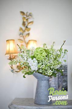 Green and white floral wedding arrangement in metal pitcher/vase