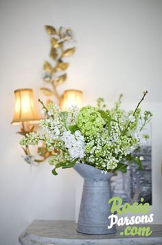 Green and white floral wedding arrangement in metal pitcher/vase