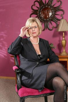 Femme assise dans un fauteuil rouge et noir, vétue d 'un tailleurs strict, jambes croisée, colier de grosse perle, petites lunettes.