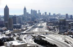 In this view looking south toward downtown Atlanta, the ice-covered interstate system is empty on a Wednesday morning, after a winter snow storm slammed the city with over 2 inches of snow that turned highways into parking lots when motorists abandoned their vehicles creating massive traffic jams lasting through January 29, 2014. (AP Photo/David Tulis)
