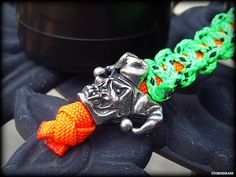 Schmuckatelli Co. Jester skull bead on a paracord and tether cord fob, attached to the cap of a storage capsule
