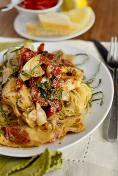 Mediterranean Smothered-Chicken - A bed of pasta and sauteed chicken with marinated roasted tomatoes, tangy artichoke hearts, briny capers, zippy lemon, fresh basil, parmesan cheese, a touch of cream, and chicken broth...