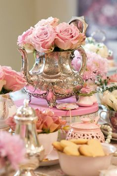 Arrangement of pretty flowers, silver, decorated tins and cookies for dessert table.