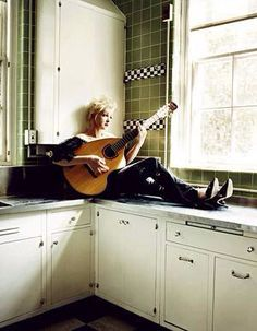 CYN playing guitar on kitchen counter in her UWS Apt.