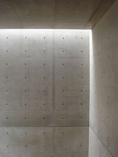 Daylight falling on the bare concrete walls of the Church of the Light by Tadao…