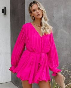 //VICI Exclusive// Romance is calling in our Found Love Pleated Romper! Featuring a fully pleated soft hot pink fabrication. Designed with a v-neckline, cuffed long sleeves and a button down front closure. The billowy fit accentuates at the waist with an adjustable fabric tie. This flirty ensemble finishes with a curly Everything Pink, Long Sleeve Romper, Ruffle Trim, Fashion 2020, Style Guides, Pink Dress, Hemline, Hot Pink, Interior Design