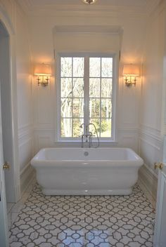Small white bathroom modeled after an old French chateau.  Double sconces. New Ravenna's Chatham tile. The Enchanted Home