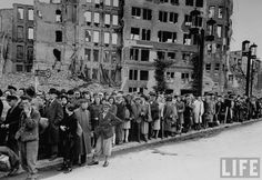 Large crowd of German citizens lined up on street waiting for bus w. bombed out buildings as a backdrop following Allied occupation of the city . Berlin . July 1945. Photo by William Vandivert