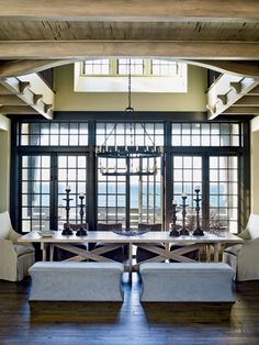 This dining room was designed to accommodate a crowd. The 12-foot long table, neutral colors, and backless benches leave a clear view of the beach, while the strong architecture makes the room interesting without complicating, fussy fabrics. (Photo: Tria Giovan)  Could have a great mountain view, too!