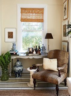 """William transformed his grandmother's console table into a chic bar that suited his style. """"I'm not crazy about a mahogany Queen Anne–style feminine piece of furniture, but it's my grandmother's. So I painted it to look like a French Provincial antique piece."""""""
