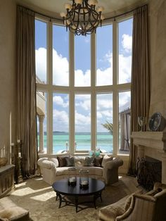 Stunning Coastal Living Room. Heaven on earth. That window looking out at the ocean is spectacular.