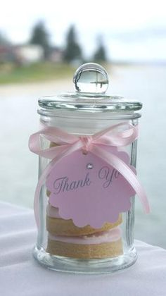Placing several cookies in jars tied with a ribbon and thank you tag, is a nice take-home gift for your wedding guests.