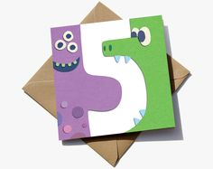 5th birthday card for a boy or girl. The number 5 is in the negative space between two cute monsters.  The cute characters have the appearance of sugar paper giving them a playful quality that children will love.