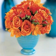 Centerpiece of orange flowers in a turquoise vase