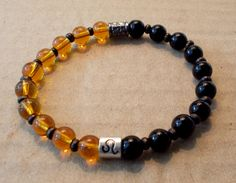 Men's Zodiac Leo Bracelet with Gold Colored Glass and Black Ceramic Beads by fancyfreeboutique on Etsy