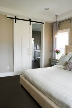 sliding doors divide without occupying space between a bedroom and bathroom