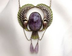 Circa 1920. This fantastic Egyptian revival Plique a jour necklace is centered by a bezel set oval scarab Amethyst . Surrounding this beautiful stone are the wings and tail of a mythical bird in beautiful green and purple plique a jour enamel. Dangling from the bottom of the necklace are two peg set amethyst drops that measure 13.15mm long and 6.30mm in diameter tapering to 2.60mm in diameter.
