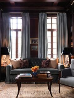Dark & Dramatic Walls    Ceiling-height curtains draw the eye up.      Traditional elements combine in this cosy space for reading or entertaining. Light drapes contrast perfectly against chocolate walls. (Dark, rich paint tones create an antiquated appearance.) Skirted furniture — a classic throwback — ceiling millwork, crystal accents and tufting on the sofa complete the look.