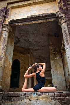 Woman doing a yoga pose in an ancient temple. Beautiful.