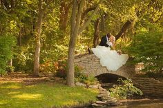 Love on the stone bridge in the gardens. Beautiful outdoor wedding in Overland Park Kansas #thekellygallery #outdoorweddings #outdoorweddingvenues