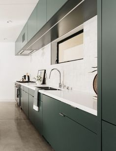 Kitchen Ideas - this modern kitchen features minimalist deep green cabinets paired with a light backsplash and countertop. #ModernKitchen #GreenKitchen #KitchenIdeas