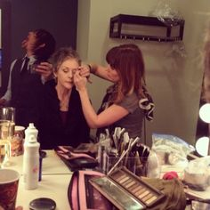 Norman Reedus taking a selfie behind Melissa McBride getting her makeup done.