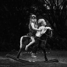 kids riding rocking horse by Tamryn Jones