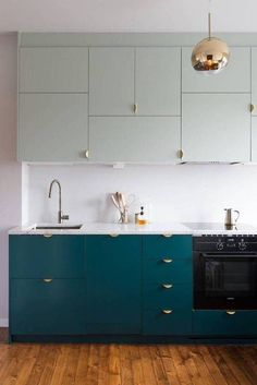 Two-tone cabinets with chic brass hardware help reinvent this streamlined IKEA kitchen into a color blocked showstopper.