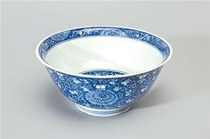 A blue and white bowl Qing dynasty, 18th century with steeply rounded sides and flared rim, painted with a continuous chrysanthemum meander of blooms and foliate scrolls in reserve on the blue ground, repeated on the interior in a central medallion and a border around the rim  17.5 cm diameter
