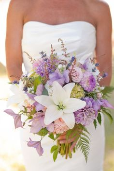 Beautiful bride bouquet with white lilies, purple flowers of many varieties and hints of green.