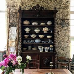 Magnificent antique kitchen hutch with dishes in a stone kitchen in a French chateau. South of France Fixer Upper Château Gudanes.