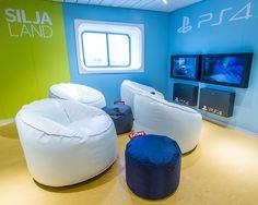 Perheen pelaajat viihtyvät uudistetussa Playstation-peliloungessa, Silja Symphony.