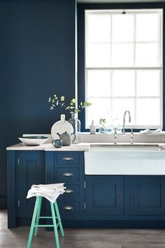 Kitchen by Designerpaint | monochromatic kitchen | navy kitchen cabinets with silver hardware | white farmhouse sink | bridge faucet | green stool | navy blue walls |