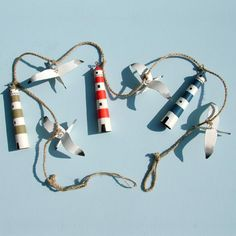This garland is made up of three hand painted tin lighthouses and 4 hand painted seagulls.