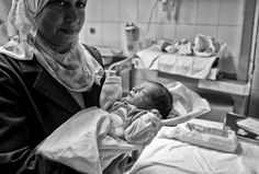 Un'infermiera tiene in braccio un neonato siriano rifugiato al Mahmoud Charity Hospital del Cairo. La sua mamma, Maram, è arrivata in Egitto due mesi fa: è scappata dalla Siria dopo che degli attacchi avevano distrutto la sua casa e ucciso i suoi vicini.  ©UNHCR/S.Baldwin