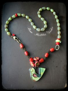 """I love the resin bird pendant by Jade Scott on this necklace and the way the ceramic flowers (Pajego Art Hous) hang in a sweet lil boquet above it. With wirewrapped red coral, green piccasso czeck glass, and lampwork accents by Ellen Dooley. This necklace is perfect for Summer! Measures 25""""."""