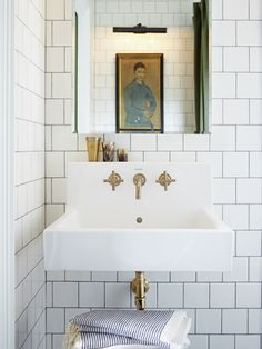 Brushed brass fixtures on the sink warm up a cool colour palette and give the room a vintage appeal. Square cut tiles laid in a brick pattern with dark grey grout make a modern statement. See more of