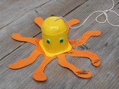 Octopus gemaakt van een kinderkwarkbakje (bv Danoontje), 2 oogjes en 8 armen uitgeknipt van karton. Voor het aan elkaar plakken een touwtje door de onderkant van het bakje prikken zodat de octopus opgehangen kan worden.