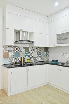 Energię do tej białej kuchni z czarnym blatem wniosły kolorowe kafle nad blatem. Wybrano różne wzory w różnych kolorach, dzięki czemu aranżacja jest bardziej efektowna. Płytki na podłodze zastąpiono za to jasnym drewnem.
