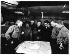 From Admiral Byrd's second Antarctic Expedition, 1933-35. This photograph was taken at Little America. Byrd (on the left) and his team are looking at a map of Antarctia.