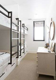 The bunk room's beds were built by Acorn Woodworking; the mirror is from Anthropologie, and the dresser is by Mr. Brown.
